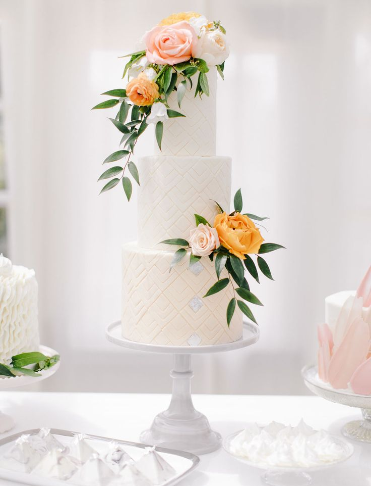 Simple modern patterned three tier wedding cake topped with orange and peach florals