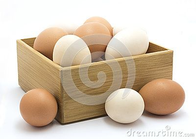 Large brown and white chicken eggs in a wooden box  against a white background.