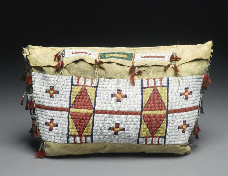 CHEYENNE BEADED HIDE POSSIBLE BAG    of typical form, sinew sewn in red, greasy yellow, blue and translucent green against a white glass beadwork ground, the front with pairs of crosses, the sides with linear elements; trimmed with tin cones inserted with red-dyed horsehair.  width 21 in.
