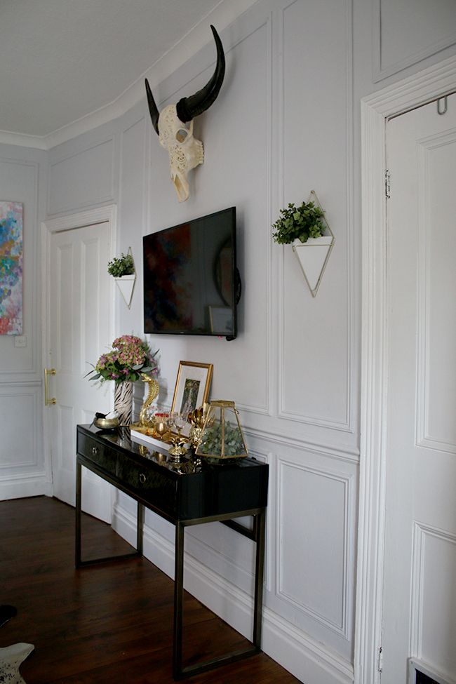 wall paneling, black console table with TV, wall planters, skull - see more on www.swoonworthy.co.uk