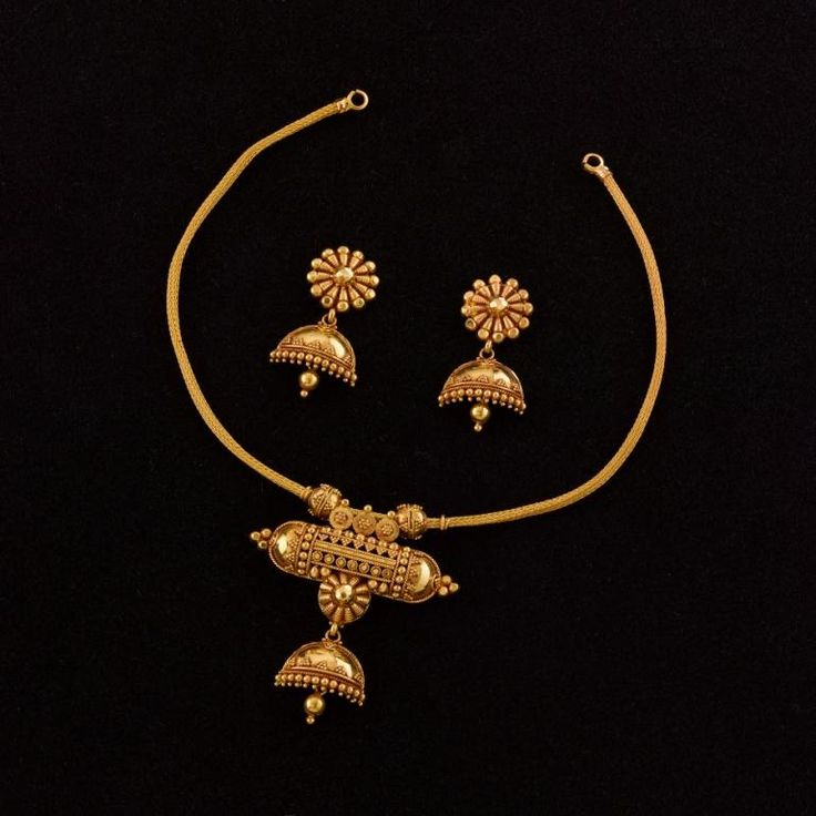 Jukti Maduli Necklace: This dainty 22K handmade gold necklace comprises a simple heley chain on which is suspended the amulet-style centrepiece from which emerges a complete half-jhumka with pasha. This fusion of a very vernacular talismanic symbol to a formal ear ornament is in itself almost revolutionary, juxtaposing the opposing worlds of mystic magic and stately culture in a grand mixture of regional styles of jewel-craft - a small bomb of an ornament that's guaranteed to attract…