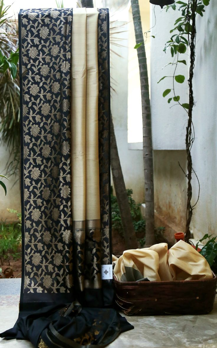 CLASSY BEIGE SOUTH TUSSAR IS UPLIFTED BY A BLACK WITH GOLD ZARI INTRICATELY WOVEN FLORAL BORDER AND PALLU GIVES THE SAREE A DAZZLING FINISH.