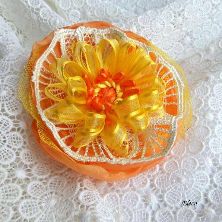 Sluneční květ Pěkný, veselý květ vyrobený zpolyesterové látky a stuhy a krajky. Průměr květu je 11 cm. Je připevněný nauniverzálním brožovém můstku, takže jde použít jak do vlasů,tak na šaty,nebo kam se vám bude líbit. Jako bonus ke každé květině dostanete zdarma skládanou origami krabičku.