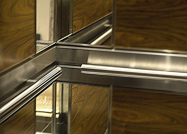 Polished Stainless Steel Tubular Handrails Anchored to a Two-Level Raised Support Band. This Elevator Interior Features Matches Quality with Durability.