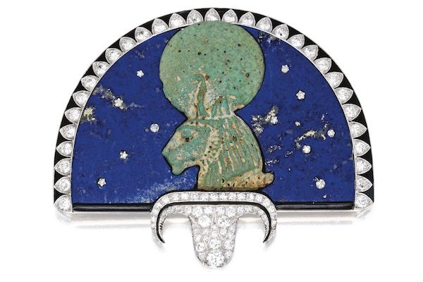 Egyptian-Revival brooch by Cartier. Circa 1923, it features an ancient green-glazed faience (a crushed quartz- or sand-based ceramic widely used in ancient Egypt) bust of Sekhmet, a goddess with the body of a woman and the head of a lioness. She is depicted with a solar disc and a uraeus (or cobra) upon her head, and these forms symbolize her status as both royalty and a solar deity.