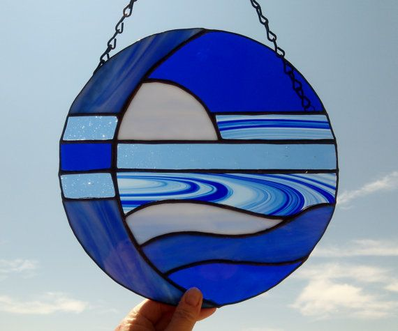 This stained glass abstract moon suncatcher is made with five diffrent shades and textures of blue glass. It measures 10 inches in diameter.