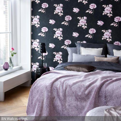 Die Tapete mit Rosen auf schwarzem Grund dominiert als Blickfang das Zimmer. Farblich darauf abgestimmt sind die lilafarbene Tagesdecke und der pastellfarbene …