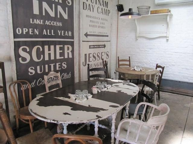 A random collection of chairs and tables gives the restaurant a homey and comfortable feel. Image via Flickr.