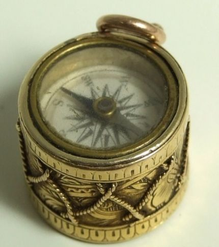 """Beautiful unmarked gold charm, stylised as a drum with inset working compass and agate. Embossed on the black ebonised base with the letter """"M"""", or perhaps a """"W"""". Size is 15mm diameter x 12mm diameter deep."""