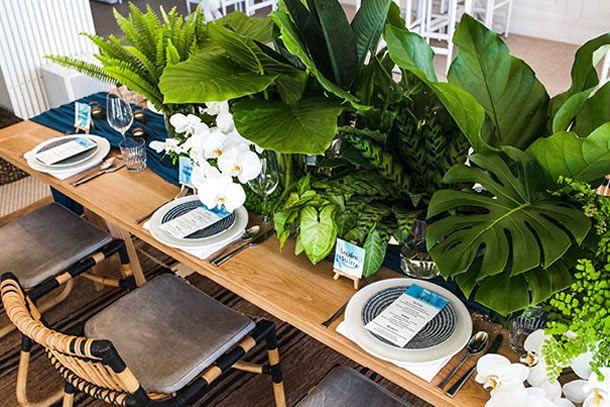 mesa posta com caminho de mesa azul petróleo, prato raso branco, prato de sobremesa azul listrado, taças de cristal e orquídeas e folhagens ao centro.