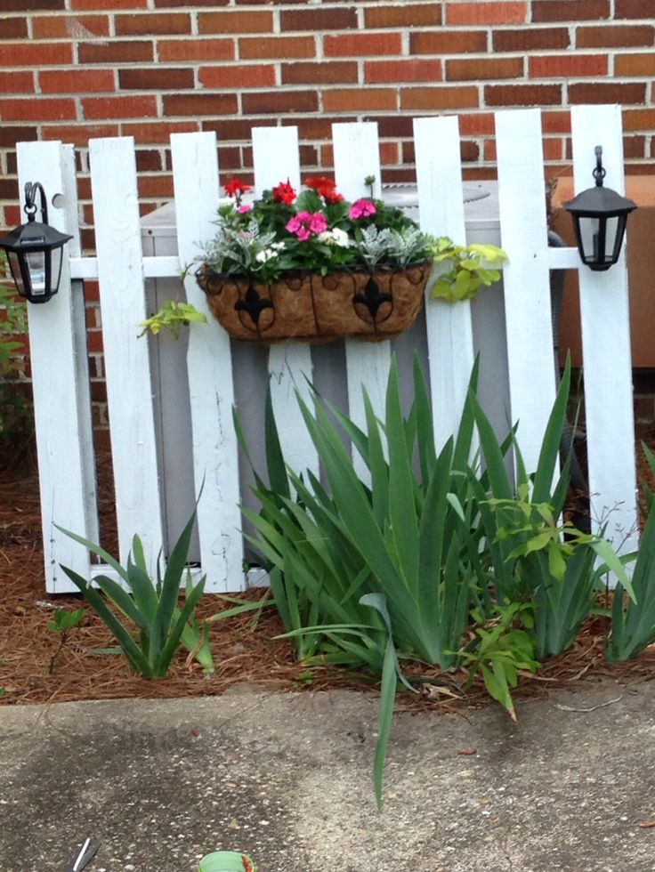 "Up cycled pallet ""Picket fence"" ac unit cover. I added a planter and dollar store solar lights."