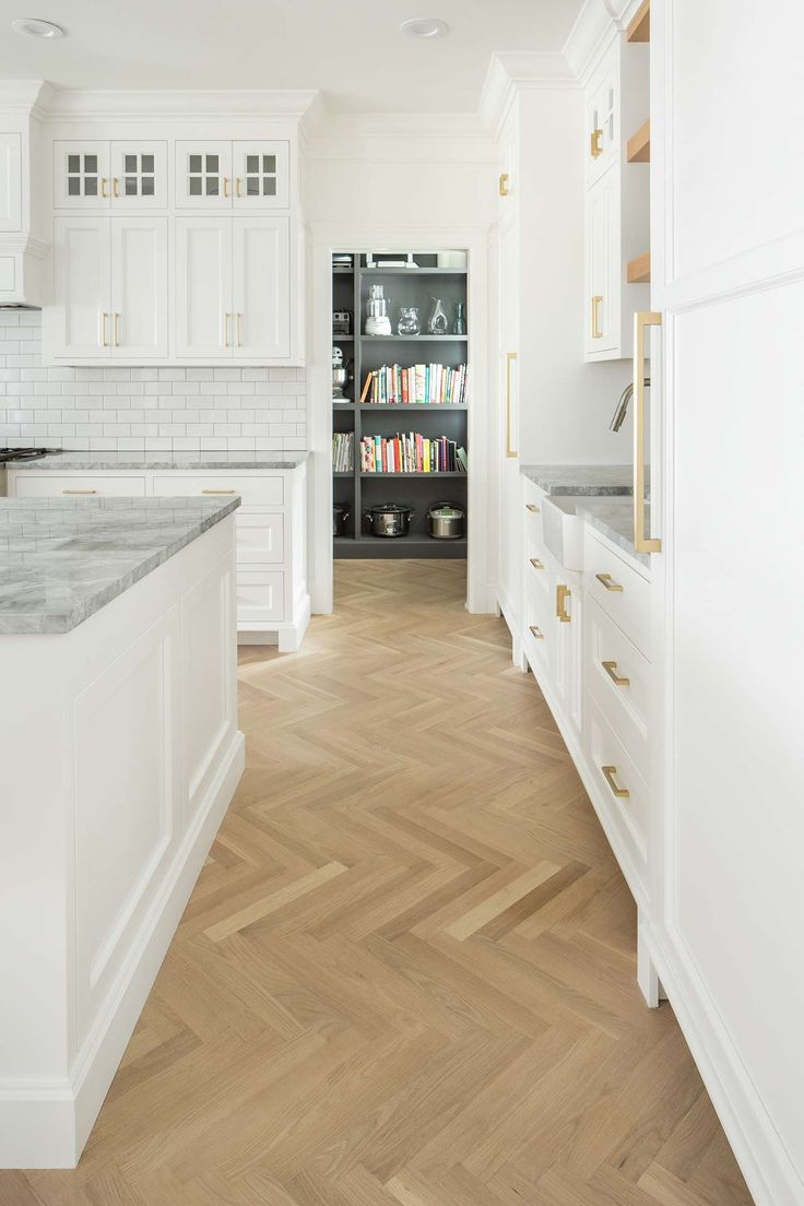 White oak hardwood flooring in herringbone pattern in white classic kitchen. White English farmhouse style home by The Fox Group. Come be inspired these English Farmhouse Style Decorating Ideas. #modernfarmhouse #englishfarmhouse #interiordesignideas #farmhousestyle #decoratingideas