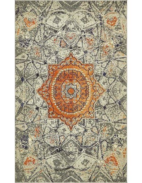 Understated and bursting with world-inspired appeal, this funky area rug lends eclectic style to any aesthetic. Machine woven in Turkey from stain-and-fade-resistant polypropylene, this alluring design showcases a Tibetan-style medallion motif in soft hues of gray with vibrant orange accents. Establish a curated ensemble in your bedroom by rolling this rug out to define the space, then place a mahogany nightstand with ornately carved legs on each side of an upholstered platform bed with a…