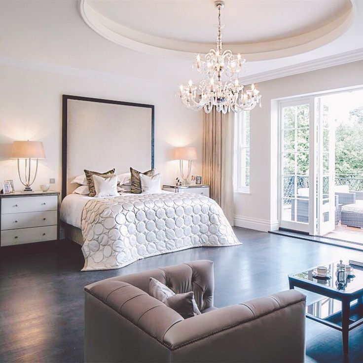 Beautiful master bedroom. Large upholstered headboard. Crystal chandelier. White, neutral bedroom.