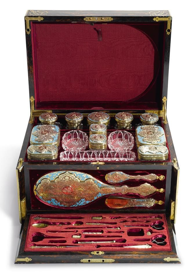 The Jewelry Lady's Store fényképe.  Victorian enameled silver-gilt and cut-glass toilet set in a brass-mounted rosewood case, Thomas Johnson I, London, 1861 - Consists of six silver-capped cut-glass boxes in sizes, four silver-capped cut-glass bottles in sizes, a silver-capped cut-glass jar, three cut-glass dishes in sizes, a large and a small hand mirror, a shoe horn, thimble, nail file, corkscrew, pocket knife, double-ended spoon, pen, propelling pencil with seal top, two pairs of…