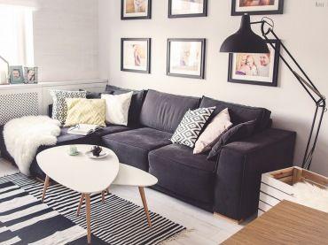 Salon w stylu skandynawskim ożywiają czarne dodatki oraz wzorzyste motywy na dywanie i poduszkach. Lekka forma mebli...