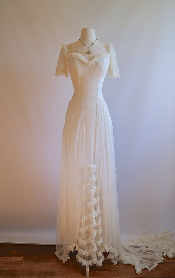This is an exquisite wedding gown from the 1930s that is so ethereal! It has a lovely, somewhat modest neckline with illusion netting and ruffles