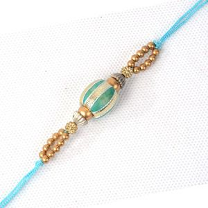 Make the festival of Raksha Bandhan memorable by sending this vibrant flower Rakhi to India from Giftblooms.com. The centre is intricately decorated with a golden bead. It has green bead at the center. Small beads are arranged to make both the ends of the thread look beautiful