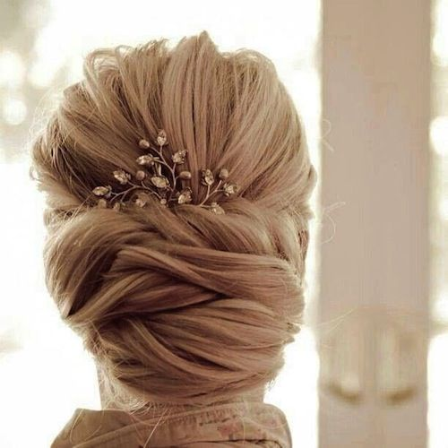 "We love the idea of this low chignon finished off with a beautiful jeweled comb. You could even use a family heirloom here such as your grandmother's brooch as your ""something old."""