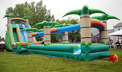 If I wasn't trying to have an affordable party, I would totally get this for Anna's party. This is way better than my sprinkler...     Nolan's Tent and Party Rental - Inflatables/Bouncers - 22' Tropical 2 Lane Water Slide with Slip & Slide