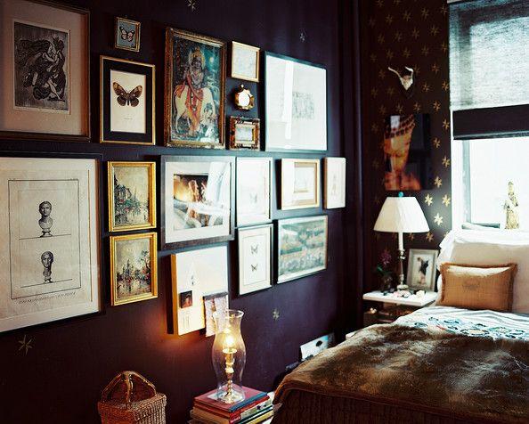 Framed pieces of art pop against a deep plum wall.  #gallerywall #art #interiordesign