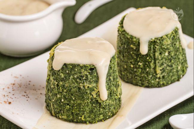Gli sformatini di spinaci sono delicati e squisiti antipasti, serviti insieme ad una gustosa crema al parmigiano.