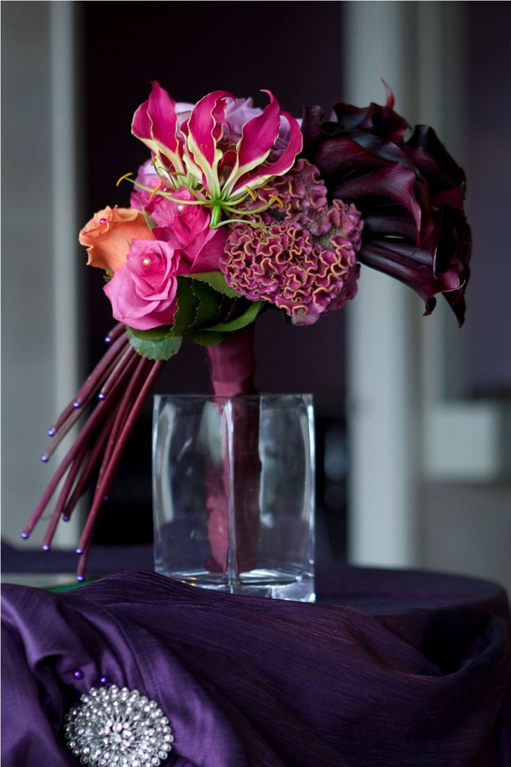 Contemporary bridal bouquet with Gloriosa lily and the purple tones with fresh green, celosia