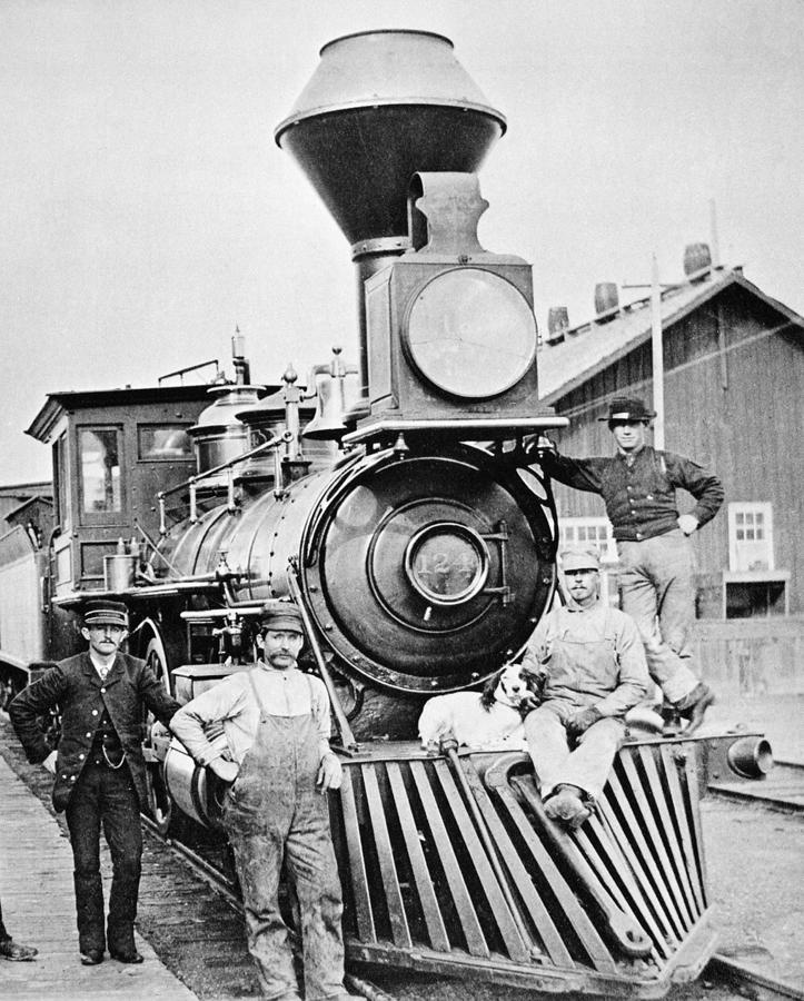 LOCOMOTIVE, 1883. The conductor, crew and canine mascot of a Central Pacific Railroad train posing by the locomotive during a station stop at Mill City, Nevada. Photographed in 1883.