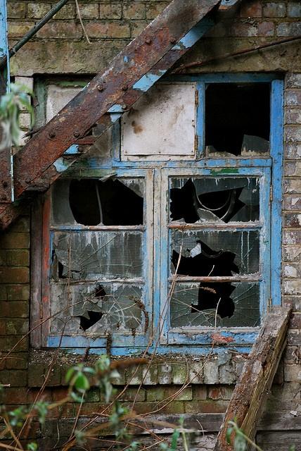 .Broken blue window in abandoned house