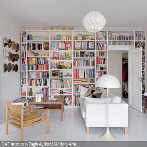 Fußboden, Sofa, Lampen, Bücherregal und Wandfarbe - alles ist Weiß. Und dennoch wirkt die Wohnzimmereinrichtung nicht kalt, da Holzmöbel und Accessoires wie …