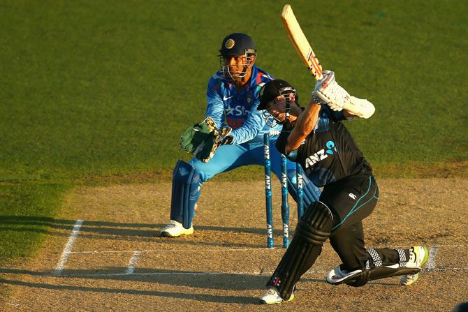 Kane Williamson of New Zealand hits a shot as Dhoni looks on © Phil Walter/Getty Images