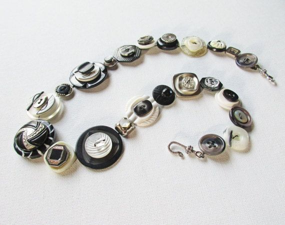 Snazzy black and white button necklace. Geometric Art Deco buttons (along with newer buttons) make this piece distinctive. Mix of textures, materials and shapes add up to a unique statement necklace. Woven with telephone wire that holds its shape, so you can adjust it for a just so fit.