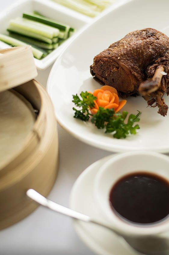 Beautiful photography of crispy duck pancakes with hoisin sauce and julienne vegetables