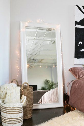 A large mirror leaning against a bedroom wall with woven rattan baskets at the side.