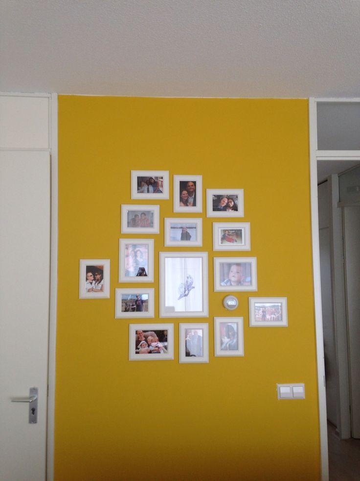 Mosterdgele muur met foto's in witte lijstjes