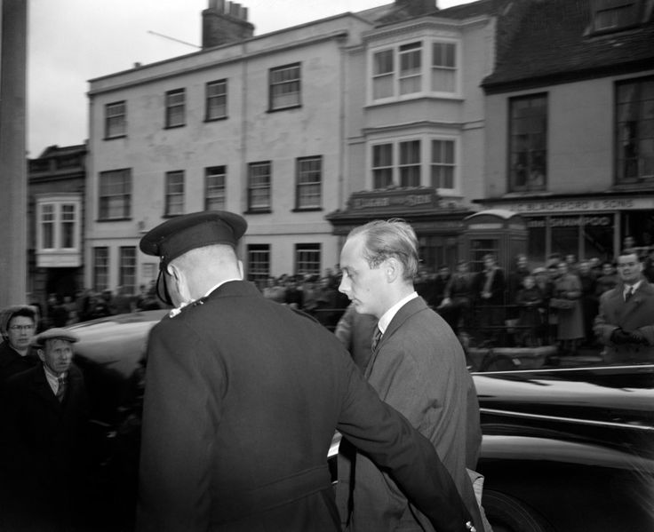 """Chief Inspector L.C Orchard leads Lord Montagu into Lymington Town Hall Court. He is charged with """"conspiracy to incite certain male persons to commit serious offences with male persons"""". Lord Montagu, former director of a London publicity firm, had returned to England only a few hours earlier from France. Ref #: PA.12517618  Date: 08/11/1953"""