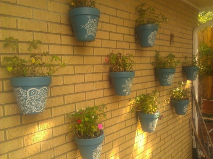 Colorful designer flower pots on a brick wall.