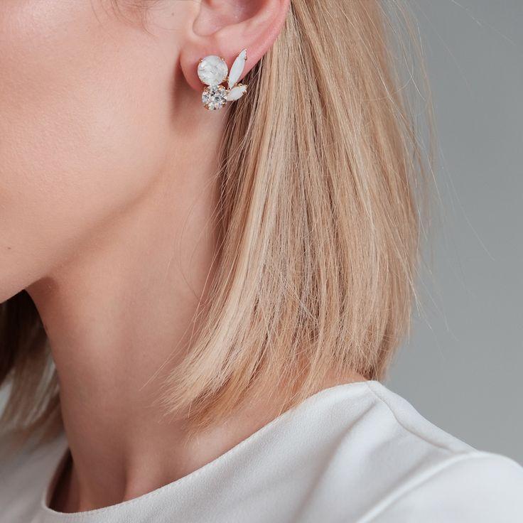 Korte, asymmetrische oorbellen op het oor met gefaceteerde glasstenen en Swarovski. Deze oorbellen kunnen evengoed overdag met losse haren of voor een gelegenheid met een strakke knot. Perfect voor je trouwdag. Deze witte oorbellen kan je als bruid dragen op de grote dag, en daarna gewoon doordragen. Super toch?