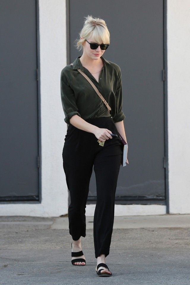 Emma Stone embraces casual style in a button down, trousers, and slide sandals.