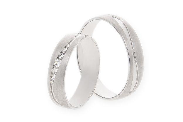 Jednoduché a přitom originální snubní prsteny jsou vyrobeny z bílého zlata. Prsteny půlkulatého profilu jsou saténově matné, pouze asymetrická drážka je lesklá. Dámský model má vsazeny jemné kamínky do drážky.