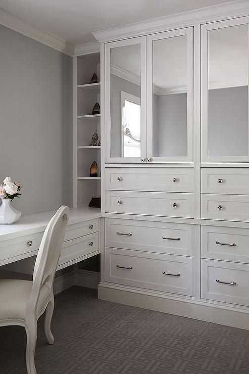 Chic dressing room features a built-in make up vanity lined with a French chair next to tall built-in cabinets accented with mirrored doors.