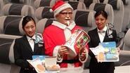 サンタクロース姿のカーネル・サンダース人形とともに、機内食「AIRケンタッキーフライドチキン」をPRする日本航空の女性社員2人=11月28日午前、東京・品川の日航本社(西川博明撮影)