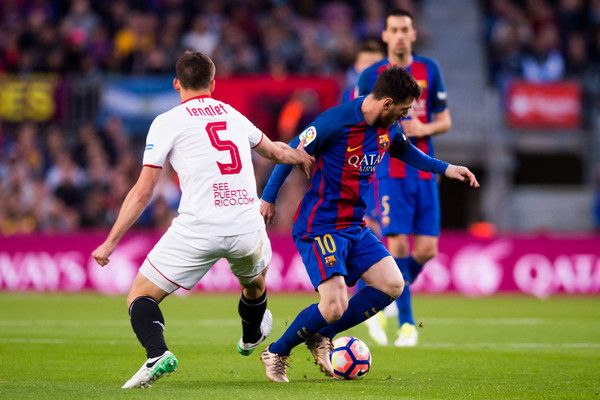 Lionel Messi of FC Barcelona conducts the ball past Clement Lenglet of Sevilla FC during the La Liga match between FC Barcelona and Sevilla FC at Camp Nou stadium on April 5, 2017 in Barcelona, Catalonia.