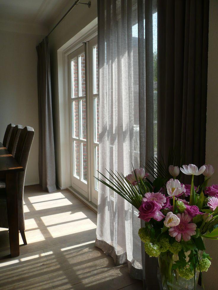 Soepele taupe-kleurige linnenlook gordijnen en als het zonnetje doorkomt krijgt de kamer een mooie zachte gloed.