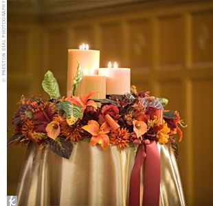 "Each pillar in the chapel was topped with a wreath packed with silk flowers. Inside each wreath were clusters of hazelnut cream candles. ""They provided a wonderful soft glow and an amazing aroma,"" says the bride."