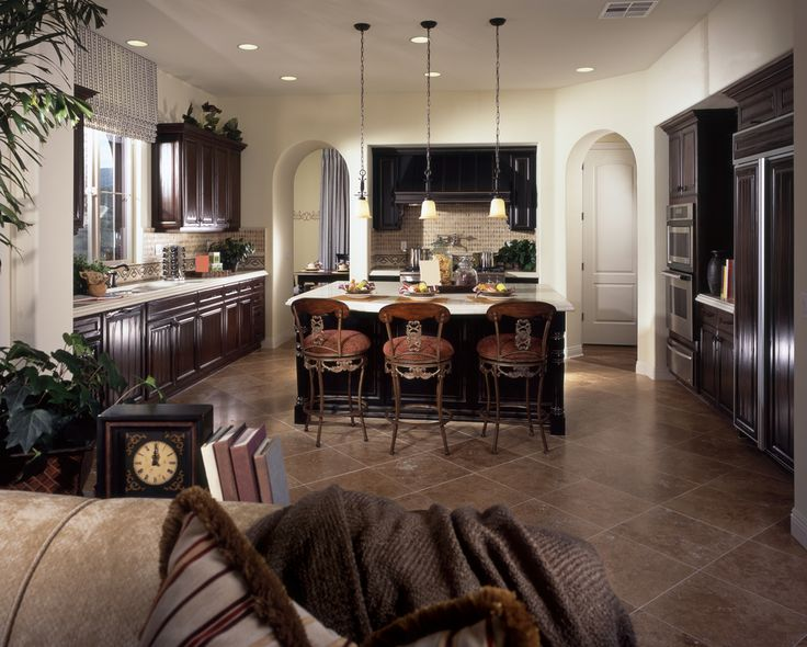 Large kitchen with white walls, arched doors, dark cabinetry, white counter tops and large central island