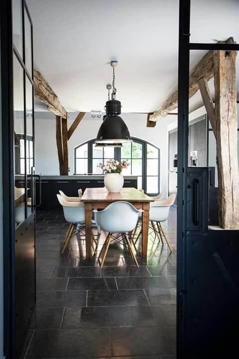 the black doors and lights frame this room but the rustic wooden table softens the space
