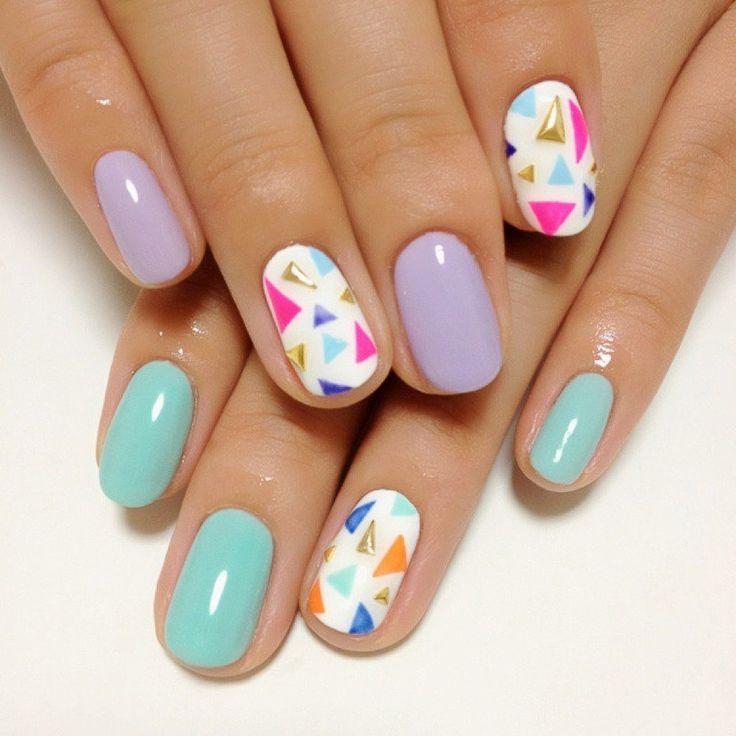 Uñas decoradas con esmalte color azul y lila y pequeñas piedras de colores