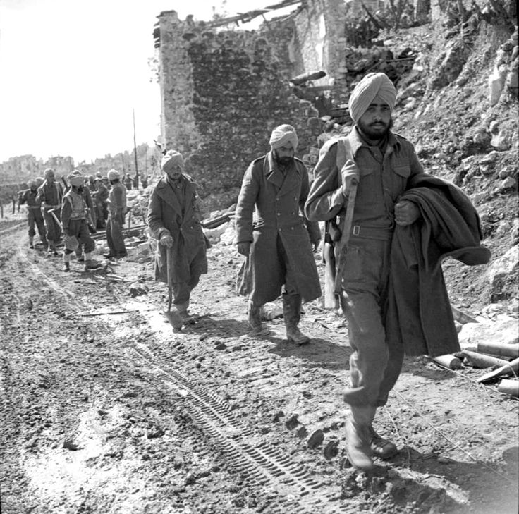 Allied Indian soldiers march passed the bomb shattered buildings on the outskirts of Cassino (Italy)