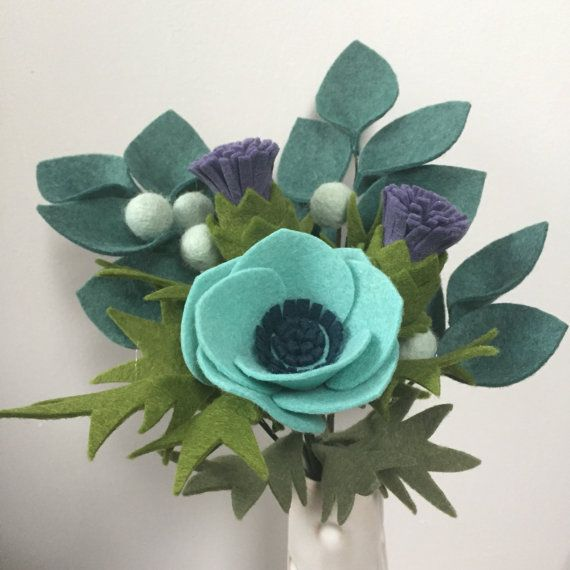 This handmade felt-flower bouquet makes a unique and beautiful gift, or centerpiece for your own home. Consisting of a single anemone, two thistles, brunia berries, and co-ordinating foliage, each bouquet is made by hand with love and care. Each flower is hand-cut from quality wool-blend felt, and formed onto wired stems that can be bent or cut to suit.